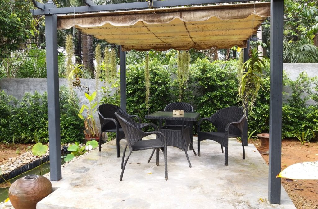 A sunny backyard patio with a canopy covering