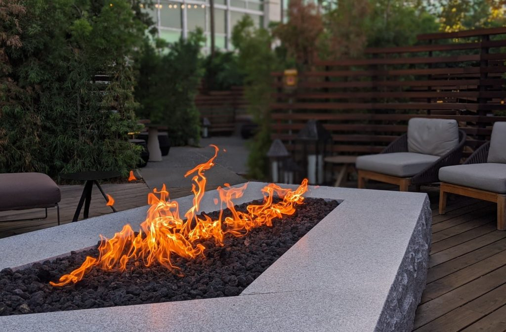 A fire table being used on a backyard patio