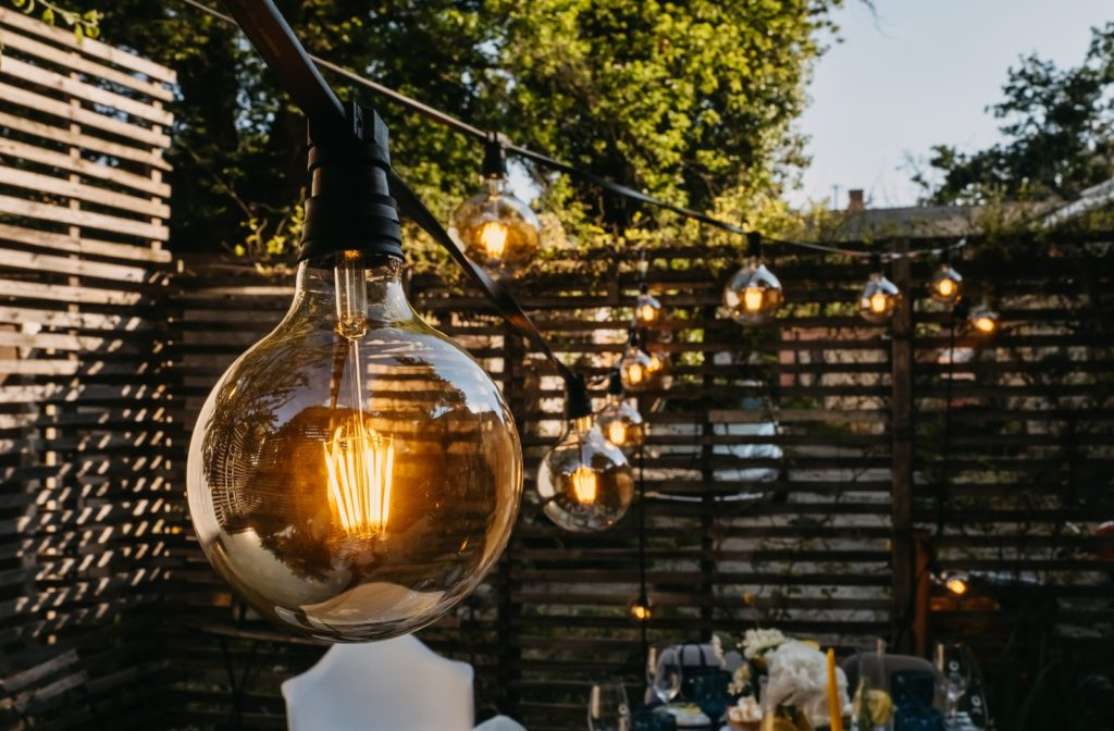A close up on an outdoor ambient light hanging over a patio