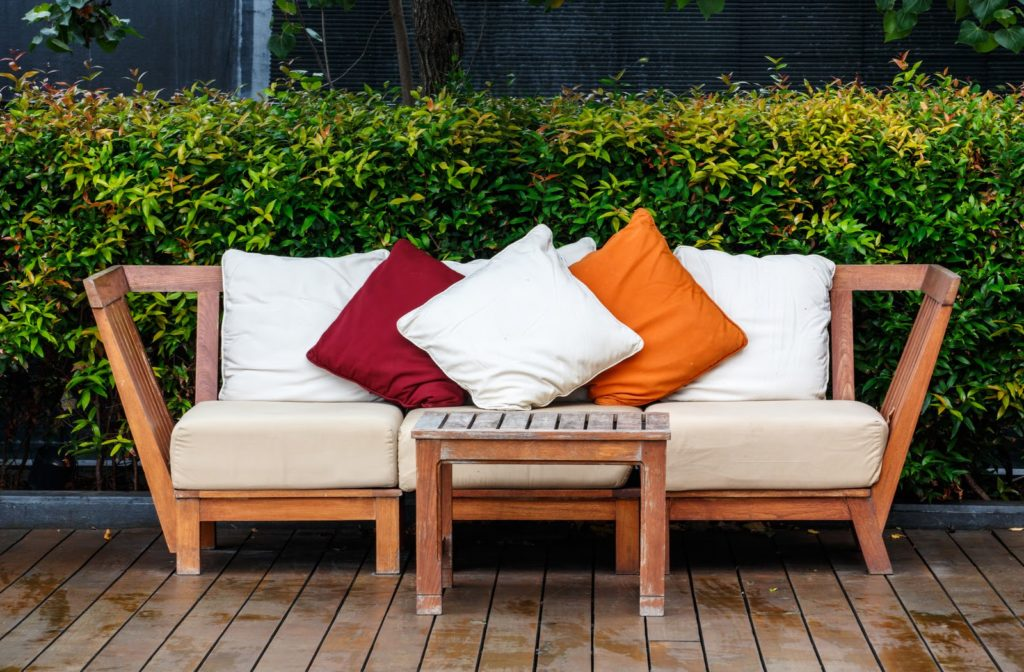 A stack of three outdoor cushions on patio furniture